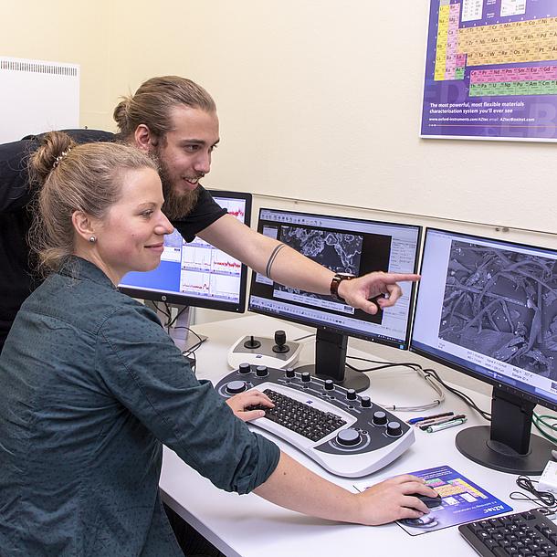 Eine Frau und ein Mann an einem Arbeitsplatz mit vielen Bildschirmen.