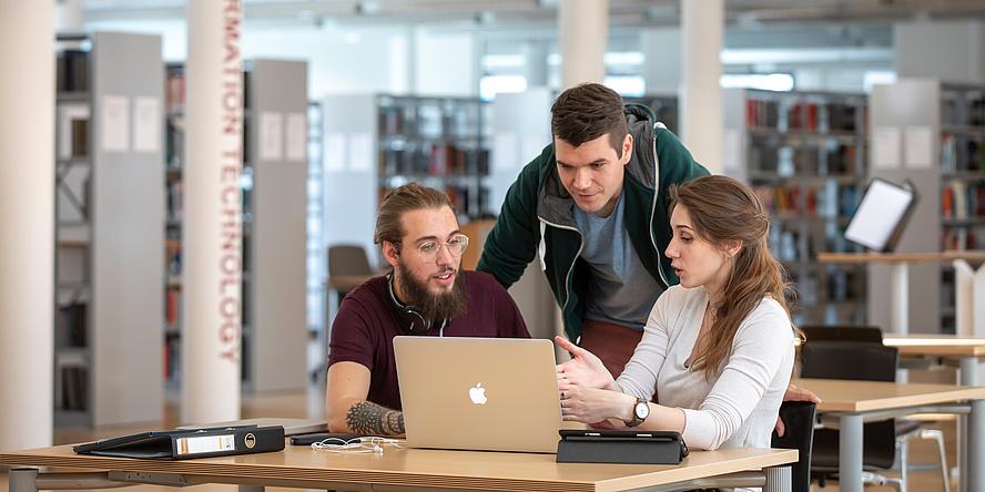 Drei junge Menschen vor einem Laptop