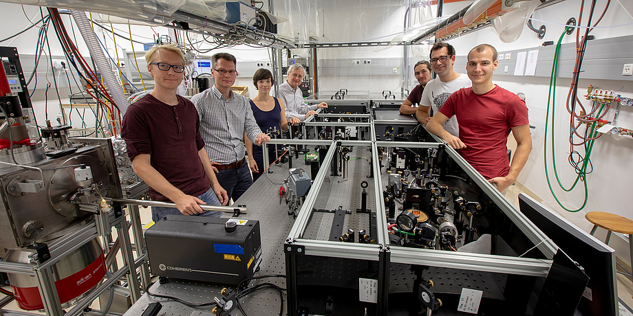 A group of researchers in the physics laboratory standing around a femtosecond laser