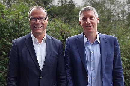 Zwei Männer in Anzug vor Gründfläche