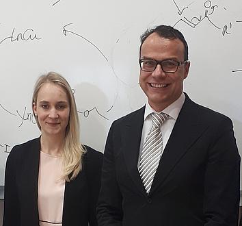 Eine junge Frau mit blonden langen Haaren und ein Mann in Anzug und Krawatte stehen nebeneinander vor einer Tafel, die mit chemischen Formeln beschrieben ist