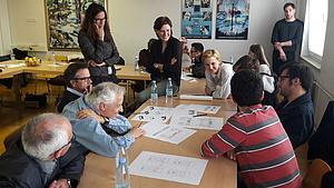 Diskussion zwischen Betreuern und Studierenden in einer kleinen Gruppe
