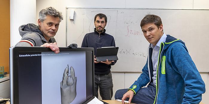 Drei Männer vor einem Computerbildschirm.
