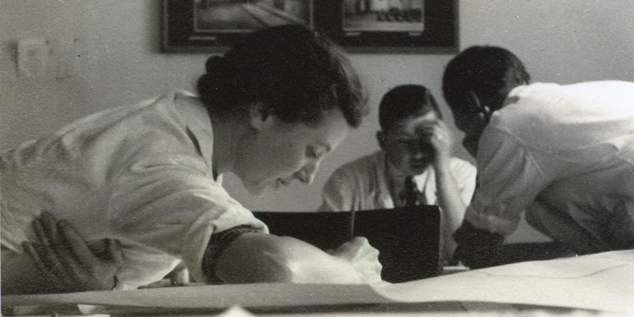 Seitenansicht von Anna Simidoff schreibend oder zeichnend über einen Tisch mit Blättern gebeugt, im Hintergrund zwei junge Männer zueinander gebeugt, ebenfalls konzentriert arbeitend.