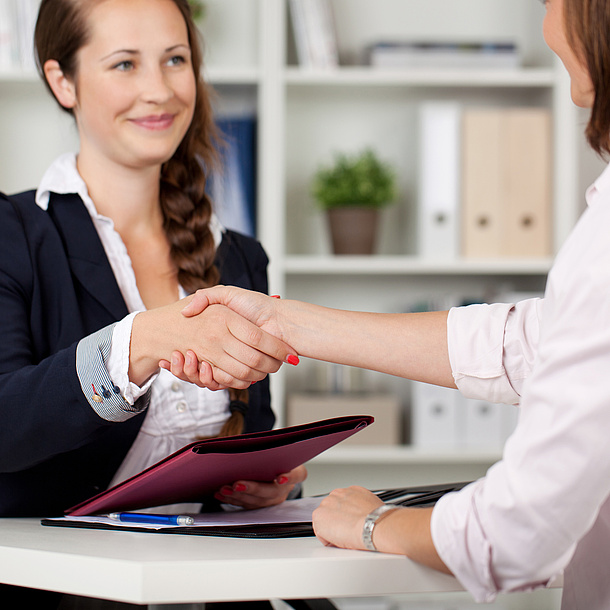 2 woman shake hands, one holds a folder in her hand