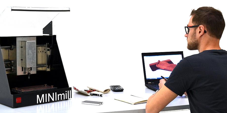 Der Student Jakob Neuhauser sitzt am Schreibtisch vor seinem Laptop, links am Tisch befindet sich die MINImill Desktop-Fräsmaschine.