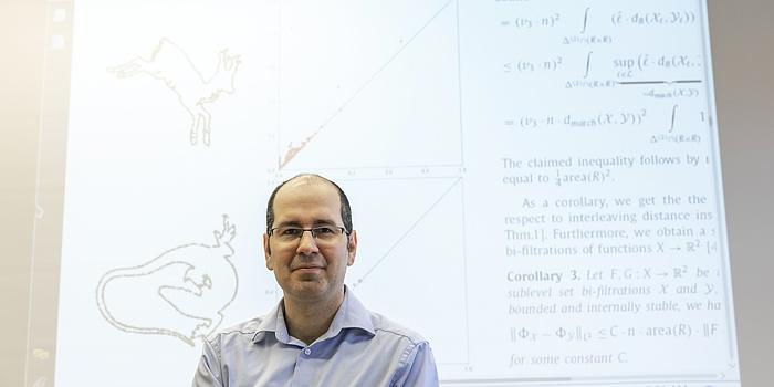 Michael Kerber steht vor einem auf die Wand gebeamten wissenschaftlichen Paper. Das Paper zeigt zwei Formen, daneben stehen Formeln.