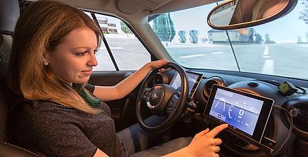 Frau am Steuer eines Autos bedient ein Navigationssystem im Cockpit