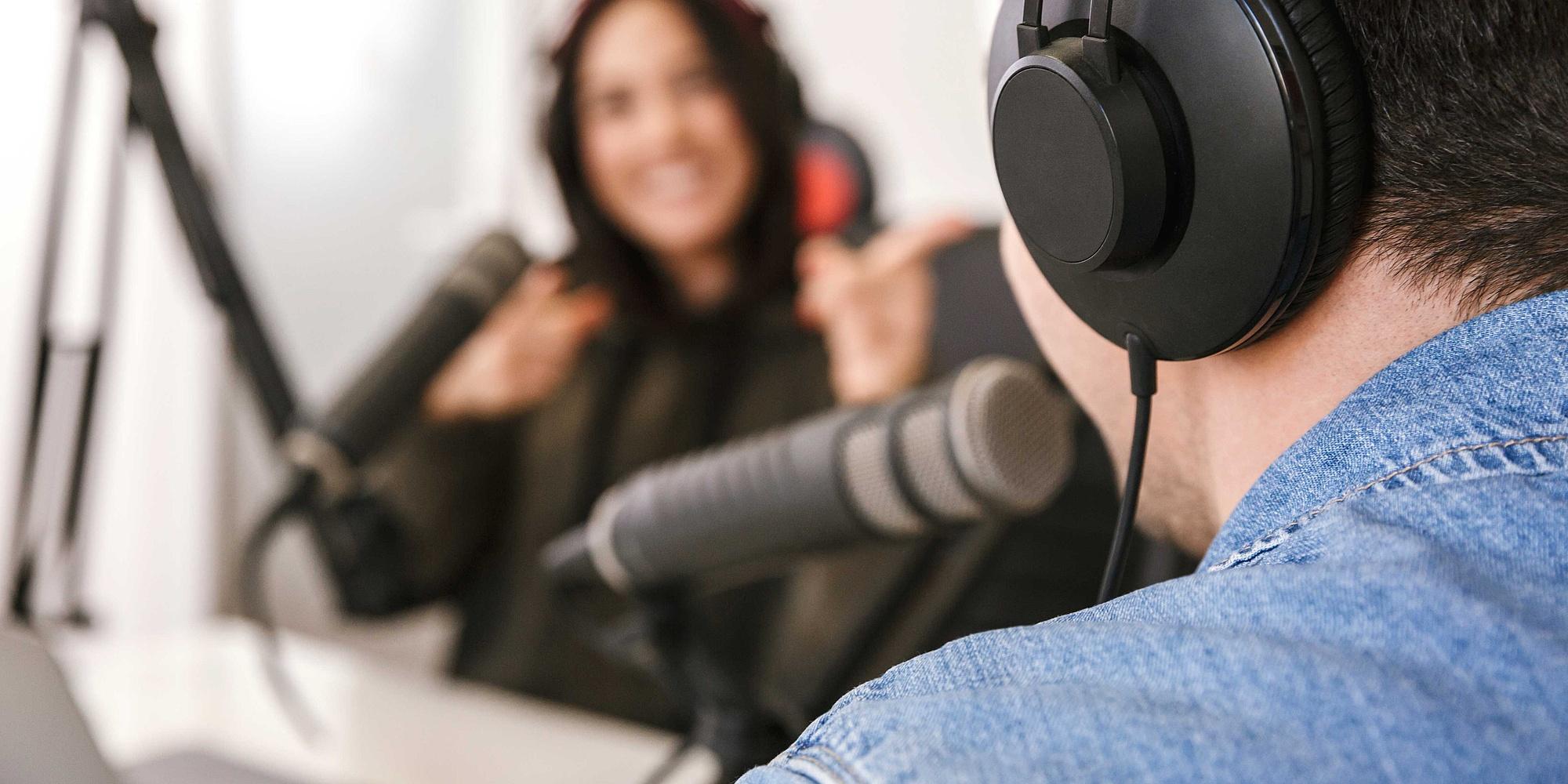 Zwei Personen mit Kopfhörer und Mikrofon