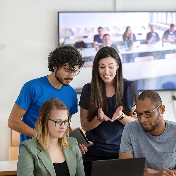 Zwei Frauen und zwei Männer im Gespräch, dahinter eine große Videowall.