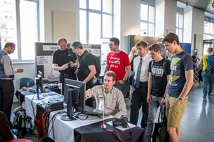 Information booths during the Linux Days. A man is demonstrating something on a computer and is being watched by visitors standing around.