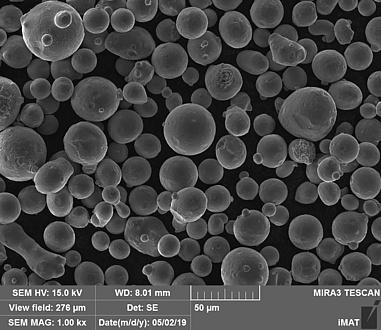 Mikroskop-Aufnahme des neuen Pulvers, viele graie Bälle auf schwarzen Hintergrund, darunter sind Daten zur Mikroskopeinstellung abzulesen