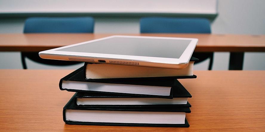 Bücherstapel und Tablet in einem Klassenzimmer