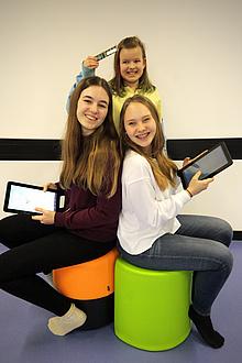 Drei Mädchen im Schulalter von 10 bis 14 Jahren präsentieren eine Computerplatine sowie zwei Tablets..