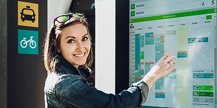 """Frau steht vor dem Touchscreen des """"tim""""-Standortes und lächelt in die Kamera."""