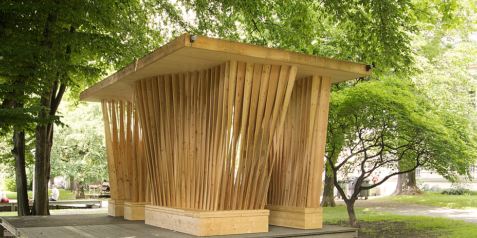 Pavilion made of wood with twisted vertical wooden slats.