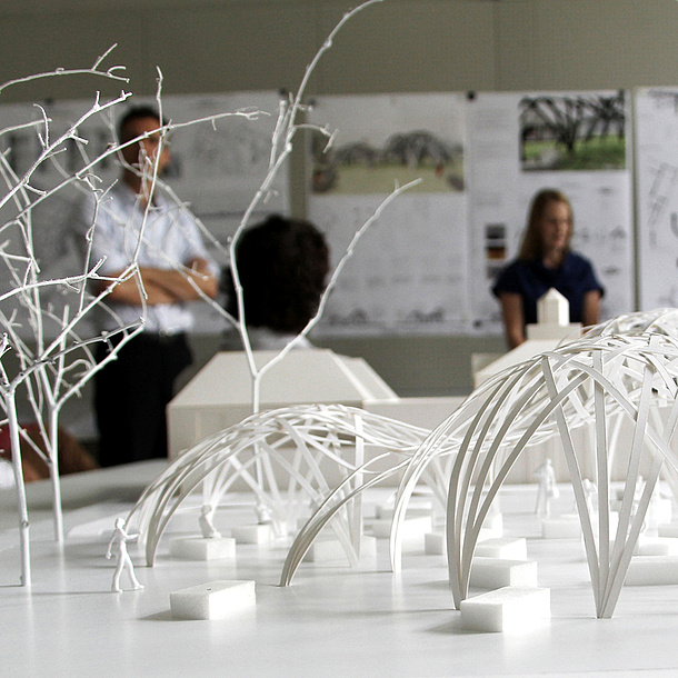 Im Vordergrund ein Architekturmodell eines Parks, im Hintergrund drei Personen. Bildquelle: TU Graz/ITE