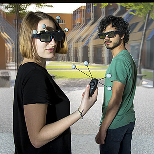 Two students with 3D glasses in a virtual room.