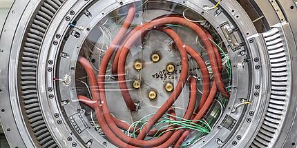 Ein Turbine Center Frame von innen. Zu sehen ist ein Kreis aus Metall mit einigen Löchern und orangen Kabeln.