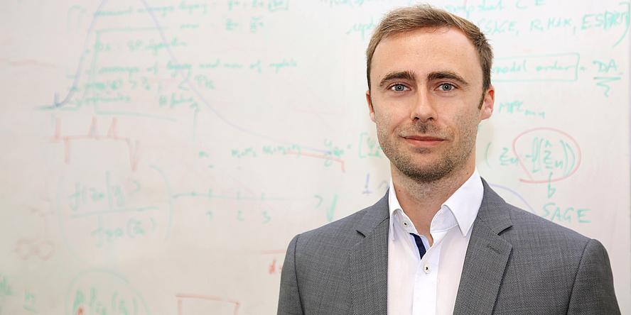 Mann vor einer Tafel mit Formeln