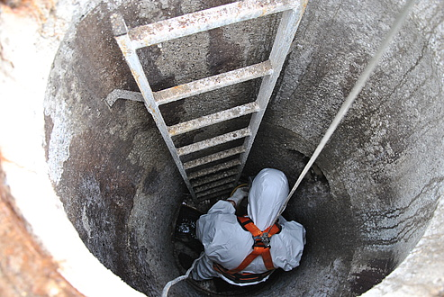 A man in a protective suit in a concrete shaft.