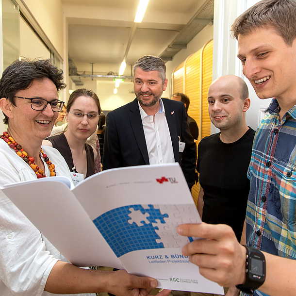 Several people regarding the guidelines for project management at TU Graz. Photo source: Lunghammer - TU Graz