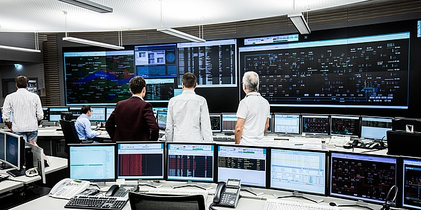 In a kind of control center many screens with different numbers and data can be seen. Three men are looking at large data projections on the back wall.