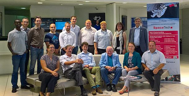 Gruppenfoto von Lehrgangsteilnehmende neben einem Plakat mit der Aufschrift SpaceTech. Bildquelle: Schrotter – TU Graz