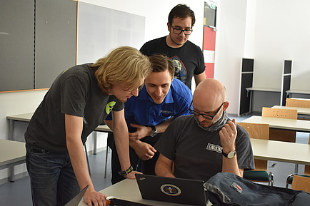four young men bend over a notebook at Linux Days and work together