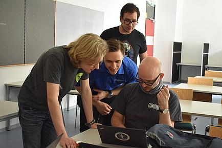 vier junge Männer beugen sich bei den Linuxtagen über ein Notebook und arbeiten gemeinsame