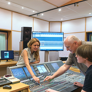 In a recording studio, two students and a teacher stand at a mixing desk.