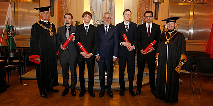 Eine Gruppe Menschen in festlichem Gewand steht in der Aula der TU Graz. Die vier Männer in der Mitte halten rote Diplomrollen in Händen.