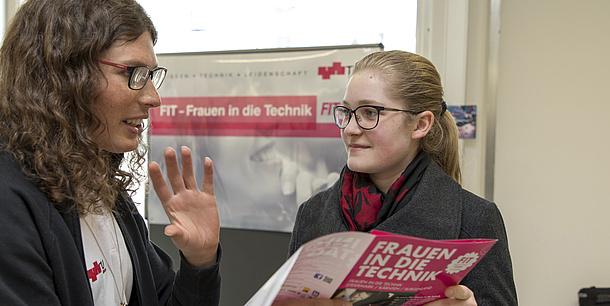 2 Frauen unterhalten sich. Eine Frau hält eine Broschüre in der Hand.