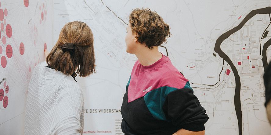 Zwei Menschen von hinten vor einem großen Plan
