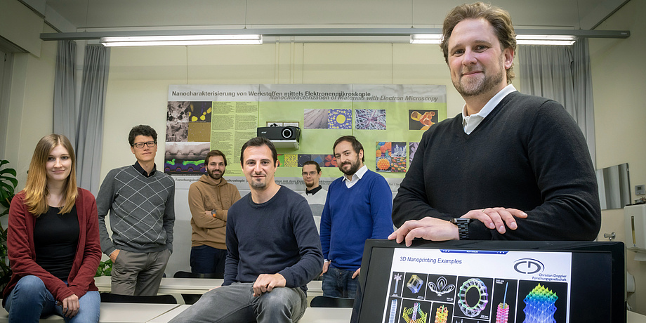 Group of people stands next to a screen with images of nanostructures on it, a poster on nanoanalytics behind them