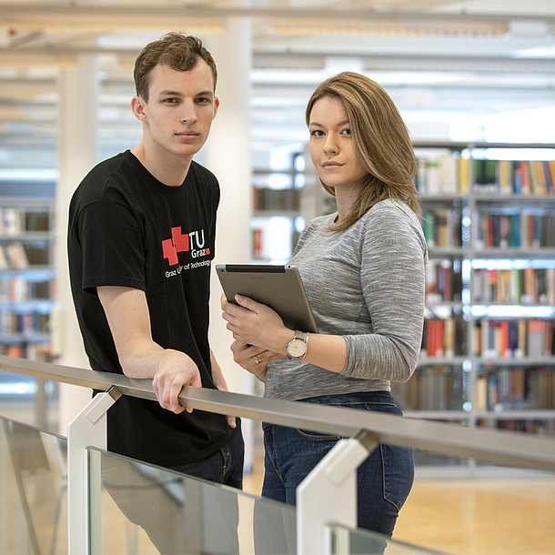 A man and a woman are standing beside a railing. In the background we can see bookshelves.