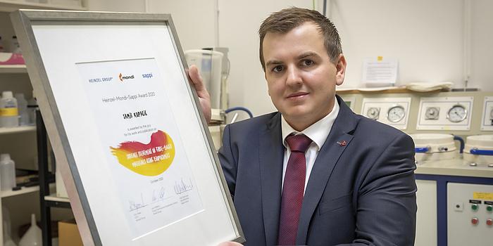 Samir Kopacic hält eine Urkunde in der Hand.