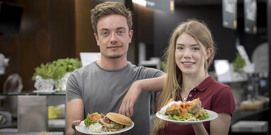 Zwei Personen stehen vor einer Küchentheke. Der junge Mann links trägt ein graues Shirt und die junge Dame rechts ein rotes. Beide halten einen Tell voll Essen in den Händen.
