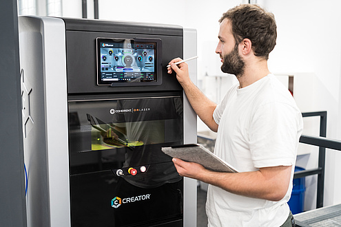 Man in front of 3D printer