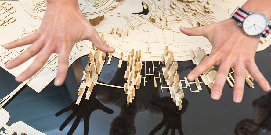 Zwei gespreizte Hände über einem architektonischen Modell aus Holz.