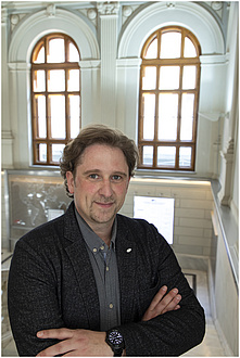 Ein Mann mit grauem Hemd lächelt, er steht vor zwei großen Fenstern.