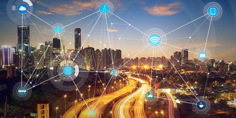 [Translate to Englisch:] Eine beleuchtete Straße und Gebäude im Hintergrund. Davor ist ein Netzwerk zu sehen mit vielen kleinen Symbolen, die unter anderem Computer, W-LAN-Symbole und Autos darstellen.