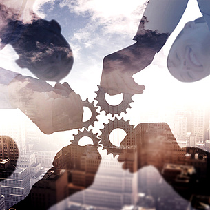 People holding together gear wheels. A building in the background. Photo source: vectorfusionart - Fotolia.com