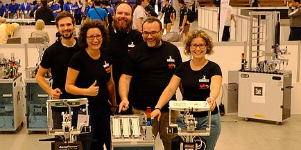 Drei Männer und zwei Frauen in schwarzen TU Graz T-Shirts posieren gemeinsam mit zwei Robotern in einer Produktionshalle