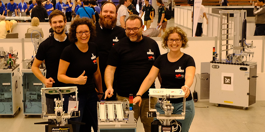 Three men and two women in black TU Graz T-shirts pose together with two robots in a production hall