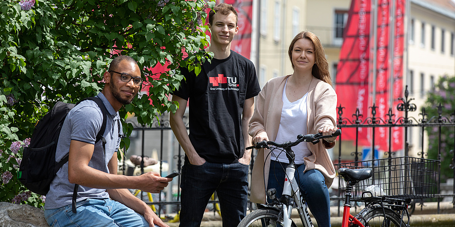 A seated student with black rucksack, a student with TU Graz shirt, standing, and a female student on a bicycle in front of wrought iron railings and red TU Graz flag on the premises of the Alte Technik.