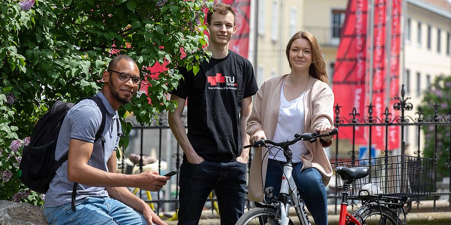 Ein Student mit schwarzem Rucksack, sitzend, ein Student mit TU Graz-Shirt, stehend und eine Studentin am Fahrrad vor dem schmiedeisernen Zaun und roten TU Graz-Fahnen am Gelände der Alten Technik.