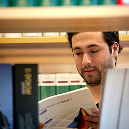 Ein Bücherregal. Dahinter ein Mann, der in einem Buch liest. Bildquelle: Lunghammer – TU Graz