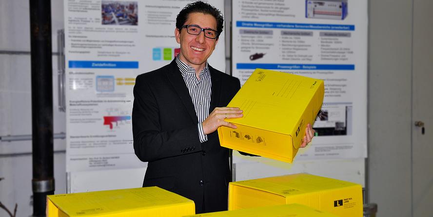 Daniel Tinello steht vor einem Paketförderband und hält eine gelbe Post-Box in den Händen.