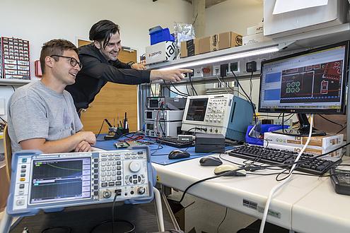 Zwei Männer an einem Tisch mit mehreren elektronischen Geräten, vielen Kabeln und kleinen Bauteilen.